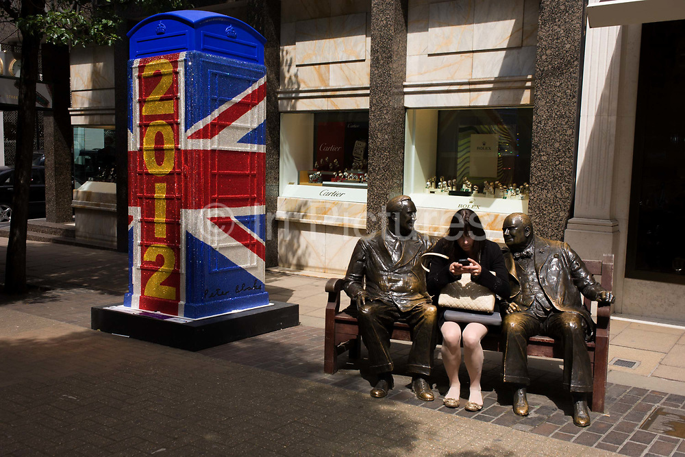 "London 19/6/12. A woman texts with statues of F.D. Roosevelt & Winston Churchill on a bench in Bond Street nr the ""Union Jack 2012"" replica artbox phone kiosk by Sir Peter Blake (artist of the Beatles 'Sergeant Pepper') and part of an art project for the Queen's Diamond Jubilee and Olympics."