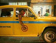A yellow taxi driver in an Ambassador car.