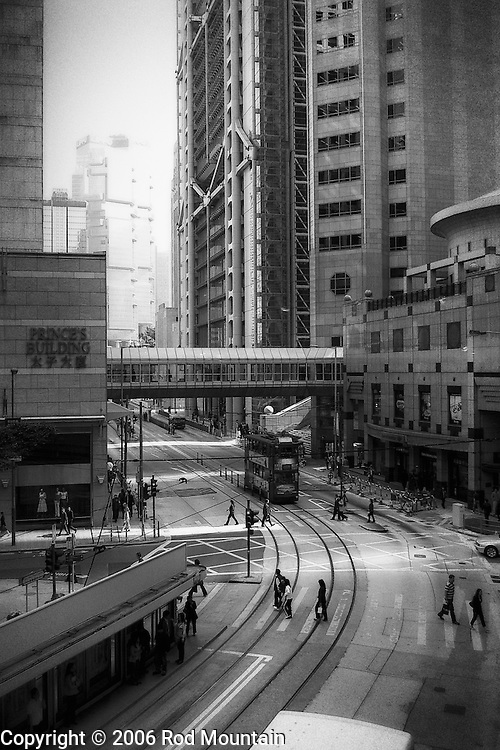 Pedestrians crossing the street near the Prince's Building in Hong Kong. I just love the cityscape of Hong Kong. One of the most interesting city walks on the planet. This image was take along Des Voeux Rd Central. The Prince's Building (https://en.wikipedia.org/wiki/Prince%27s_Building) is on the left and we can see the HSBC Building (https://en.wikipedia.org/wiki/HSBC_Building_(Hong_Kong)) in the background. <br /> <br /> Image: © Rod Mountain<br /> www.rodmountain.com