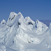 Rime-coated peaks rise above fjords & icecaps of southern Chile.