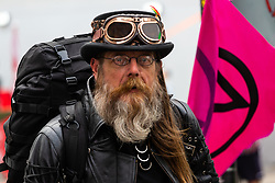 A man wearing 'steam punk' clothing wanders through the crowd as hundreds of environmental protesters from Extinction Rebellion occupy Oxford Circus, a pink yacht being the focal point of their presence, with traffic denied access to two of London's busiest streets. London, April 16 2019.