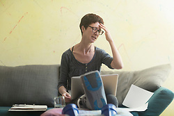 Stressed woman with broken leg and laptop working from home