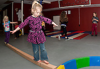 Bailey Quimby followed by Becca Buttermore hone their balance beam skills during Artsfest's Circus and Performing Arts for Kids at Laconia Community Center Monday afternoon.  (Karen Bobotas/for the Laconia Daily Sun)