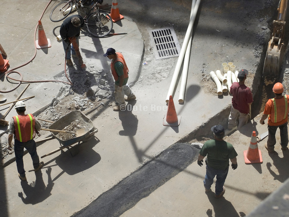 Construction workers breaking up the street to put some piping underground.