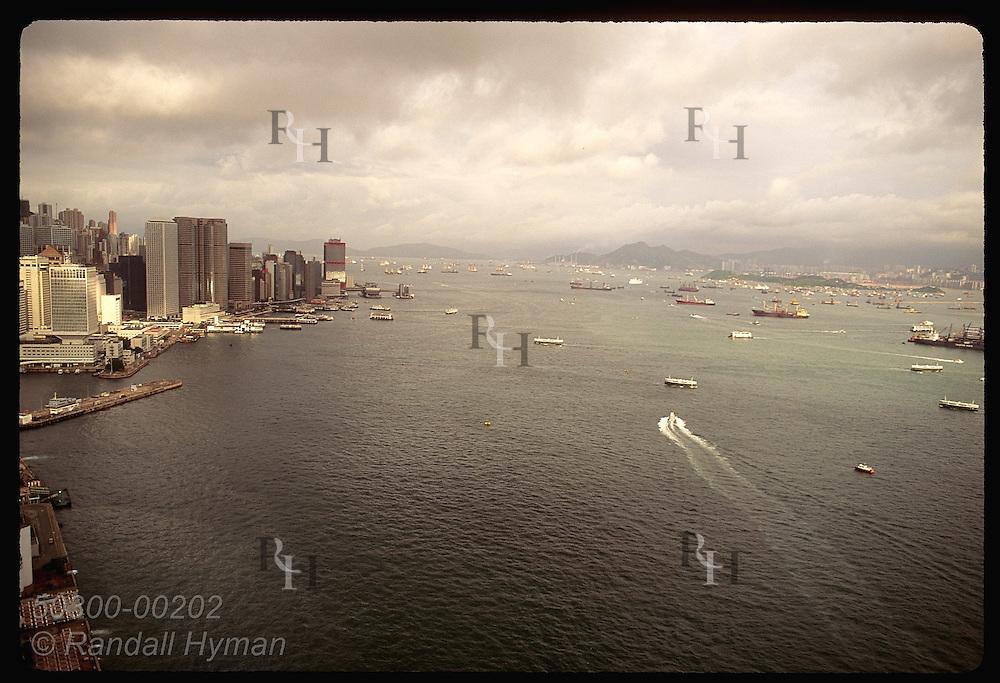 Yacht cuts a wake between Kowloon & HK headed west in early morn thru Hong Kong harbor; aerial. Hong Kong
