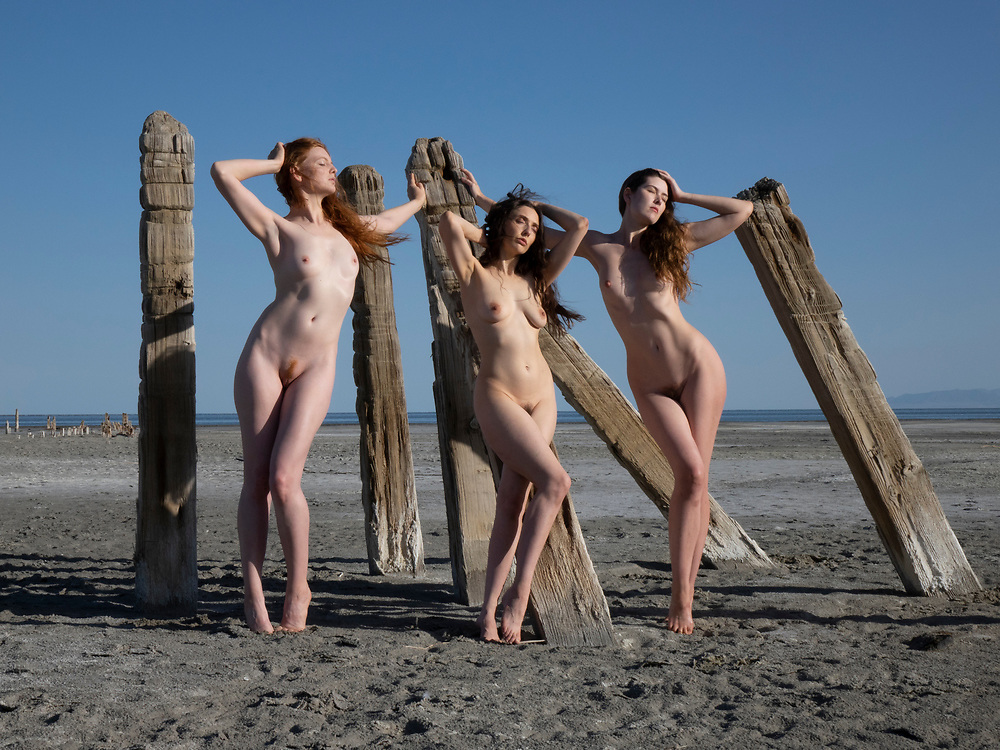 Three nude women posing with a group of old lake pilings at the Great Salt Lake, Utah