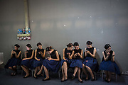 Exhibit hostesses sit using smartphones during the China Guangzhou International Automobile Exhibition in Guangzhou, China, on Friday, Nov. 20, 2015.