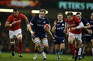 Jonny Gray of Scotland © makes a break past Aaron Shingler (l) and Rhys Patchell of Wales ® and heads towards the try line within the 1st few minutes of the match. Wales v Scotland, NatWest 6 nations 2018 championship match at the Principality Stadium in Cardiff , South Wales on Saturday 3rd February 2018.<br /> pic by Andrew Orchard, Andrew Orchard sports photography
