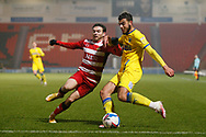 Nesta Guinness-Walker of AFC Wimbledon  beats Doncaster defender Reece James during the EFL Sky Bet League 1 match between Doncaster Rovers and AFC Wimbledon at the Keepmoat Stadium, Doncaster, England on 26 January 2021.