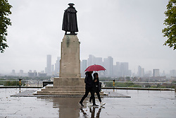 © Licensed to London News Pictures. 27/07/2021. London, UK. Members of the public use an umbrella to shelter from rain in Greenwich Park in South East London. A yellow weather warning for thunderstorms is in place for parts of England. Photo credit: George Cracknell Wright/LNP