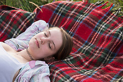 Close-up of a young woman sleeping on blanket, Bavaria, Germany
