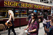 Tourists walk towards a Sightseeing tour of London bus parked up ready to take on passengers for a trip around the sights on London. This is a popular tour company enabling tourism throughout the capital.