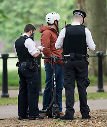 © Licensed to London News Pictures. 22/06/2021. London, UK. Police officers stop and question a man using an electric scooter on a public road near Buckingham Palace in Westminster, London. The use of privately owned e-scooters remains illegal except for on private land. A number of rental schemes are currently being trialed across the UK. Photo credit: Ben Cawthra/LNP