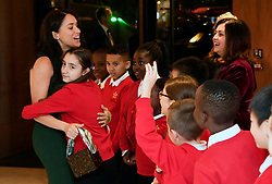 The Duchess of Sussex is embraced by a member of Star Primary School Choir during the annual WellChild Awards at the Royal Lancaster Hotel, London.