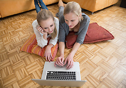 Mother and daughter using laptop, smiling