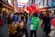 Chinese New Year on Gerrard Street, Soho, London. Also known as Chinatown. Local Chinese community gather on this famous area of central London which is the focus of celebrations for this, the Chinese Year of the Dragon, so a most auspicious year ahead. Bright red and yellow lanterns are strung across between the buildings creating a canopy of colour.