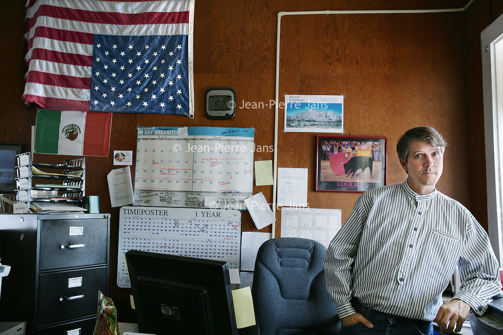 Verenigde Staten.Tombstone.Arizona. juli 2005.<br /> Chris Simcox ( hier in zijn kantoor in Tombstone, voorman van het Minuteman Civil Defense Corps, een groep van burgers, patrionetten, die het opnemen tegen het wettig gezag en vrijwillig de grens willen bewaken tussen de VS en Mexico.<br /> Voornamelijk uit ouderen bestaande Amerikanen die de grenzen van de Verenigde Staten bewaken tegen illegale indringers.Amerikaanse vlag.Mexicaanse vlag.Kantoor.Kalender.Grens.Grensproblematiek.Grenzen dicht.<br /> Chris Simcox (here in his office in Tombstone, leader of the Minuteman Civil Defense Corps, a voluntary group that guards the border.<br /> Archives 2005. From series of chase by police on illegal Mexicans who cross the border in Arizona.