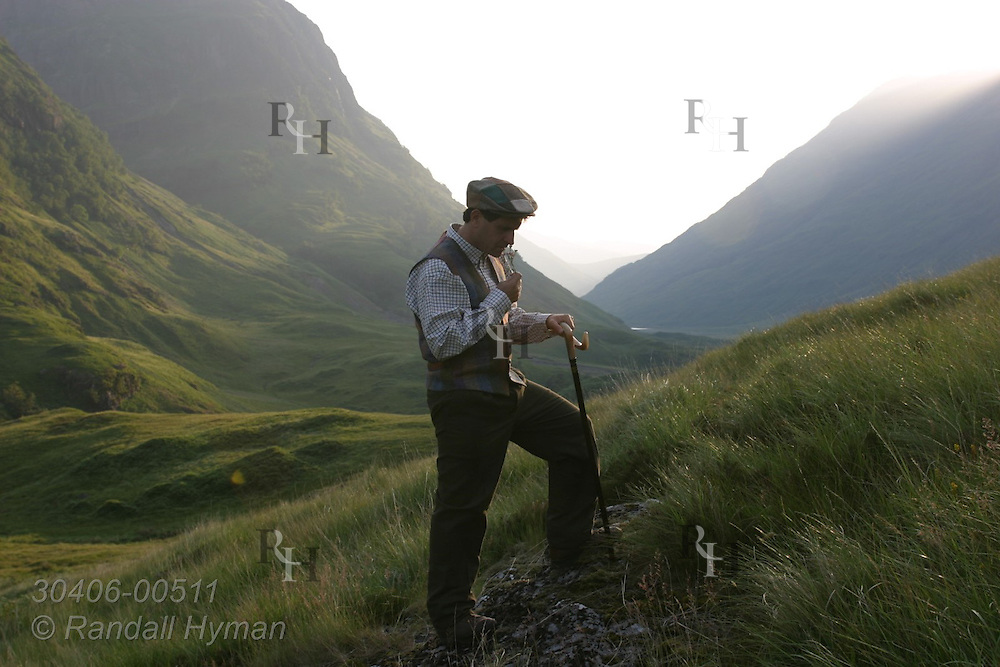 Man in traditional hiking outfit smells flower in grassy field of upper Glen Coe on a July afternoon; Glencoe Scotland.