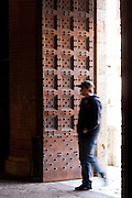 A tourist passes through the massive door of Palazzo Pubblico, the gateway to climbing the famous Torre del Mangia, Siena, Tuscany, Italy.