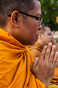 20 OCTOBER 2012 - BANGKOK, THAILAND:  A Buddhist monk chants and prays at a special alms giving ceremony. More than 2,600 Buddhist Monks from across Bangkok and thousands of devout Thai Buddhists attended the mass alms giving ceremony in Benjasiri Park in Bangkok Saturday morning. The ceremony was to raise food and cash donations for Buddhist temples in Thailand's violence plagued southern provinces. Because of an ongoing long running insurgency by Muslim separatists many Buddhist monks in Pattani, Narathiwat and Yala, Thailand's three Muslim majority provinces, can't leave their temples without military escorts. Monks have been targeted by Muslim extremists because, in the view of the extremists, they represent the Thai state.         PHOTO BY JACK KURTZ