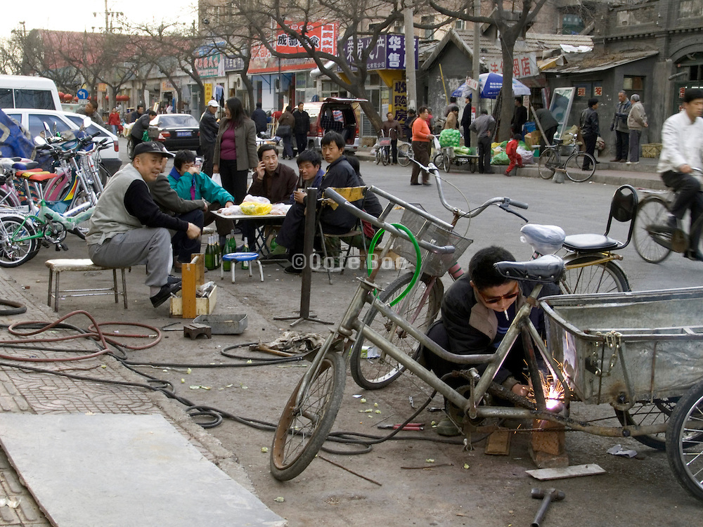 A man repairing bicycle carts in the street Beijing China