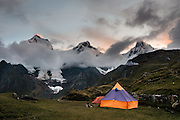 """Dusk falls over Cordillera Huayhuash at Lake Carhuacocha campground (13,600 feet) in Andes Mountains, Peru, South America. Peaks from left to right are: Yerupaja Grande (21,770 ft, highest point in the Amazon watershed), Yerupaja Chico, and Mount Jirishanca (""""Icy Beak of the Hummingbird""""). Day 2 of 9 days trekking around the Cordillera Huayhuash."""