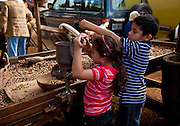 Children try a hand seperator on freshly harvested coffee beans at the Mariaco Coffee Festival in Puerto Rico.
