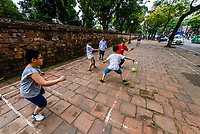 Boys playing kickball on a sidewalk in Hanoi, northern Vietnam.