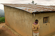 A youth stands alone near a home in the Nyamagabe District of Rwanda's Southern Province. The Mudasomwa Area Development Program (ADP) located here is one of many long-term development initiatives led by the international nonprofit World Vision. Area Development Programs work within communities like Nyamagabe over a period of several years, providing developmental resources to foster long-term, sustainable growth in the economic and physical well being of the community.