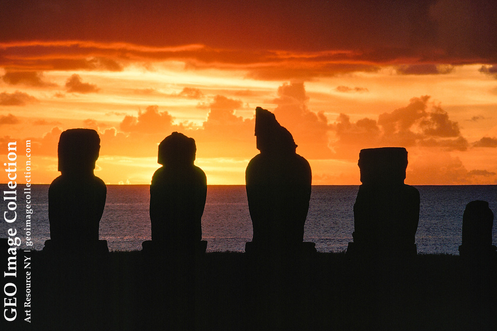 Ancient statues are silhouetted against a sunset sky.