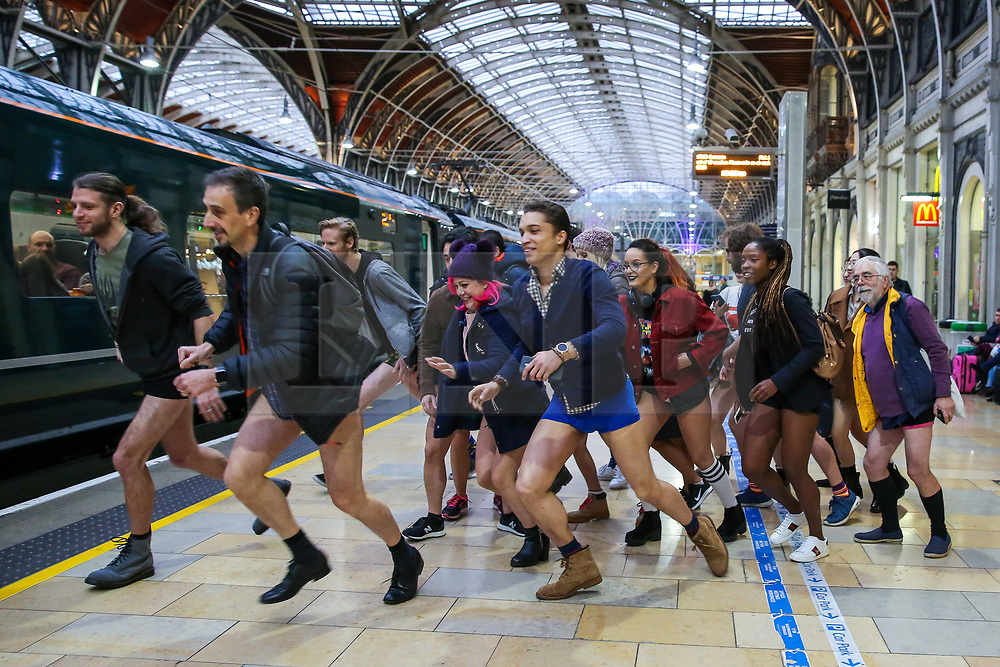 """© Licensed to London News Pictures. 13/01/2019. London, UK. Participants take part in 10th anniversary of 'No Trousers Tube Ride' by having fun and games at Paddington Station. The """"No Pants Subway Ride"""" is an annual event staged by Improve Everywhere every January in New York City. The mission started as a small prank with seven guys and has grown into an international celebration of silliness, with dozens of cities including London around the world participating each year. Photo credit: Dinendra Haria/LNP"""