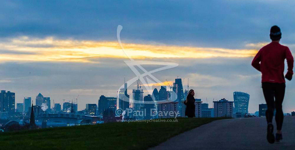 London, November 30 2017. A runner reaches the summit of Primrose Hill as the sun rises over the London skyline on a chilly London morning when overnight temperatures plunged to below freezing. © Paul Davey