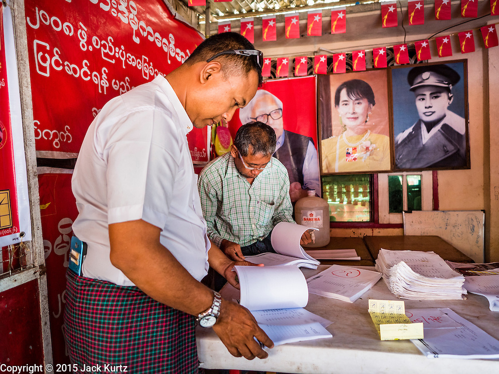 02 NOVEMBER 2015 - YANGON, MYANMAR: A Burmese voter (left) looks for his name on a list of voters at a NLD campaign outreach office in Mingaladon, a township in Yangon. Voter registration rolls were released Monday. Voters and party officials are double checking rolls to ensure accuracy. Photos of NLD leader Aung San Suu Kyi and her father, Gen Aung San, Myanmar's national hero, credited as being the father of Burmese independence are on the wall behind him. National elections are scheduled for Sunday Nov. 8. The two principal parties are the National League for Democracy (NLD), the party of democracy icon and Nobel Peace Prize winner Aung San Suu Kyi, and the ruling Union Solidarity and Development Party (USDP), led by incumbent President Thein Sein. There are more than 30 parties campaigning for national and local offices.     PHOTO BY JACK KURTZ