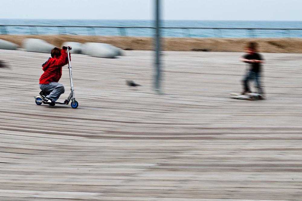 Scooter kids on promenade deck in Tel-Aviv