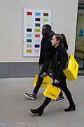 Shoppers carrying a yellow bag from Selfridges department store walks past a colour swatch on the wall of a central London business, on 22nd November 2017, in London England.