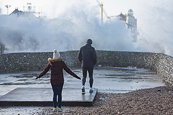 © Licensed to London News Pictures. 23/02/2017. Brighton, UK. Members of the public watch powerful waves hit Brighton Pier as storm Doris is hitting Brighton and Hove with powerful gusts of wind up to 50 mph. Photo credit: Hugo Michiels/LNP