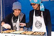 East London July . Brick Lane, Sunday morning. Young Japanese men cooking octopus balls.