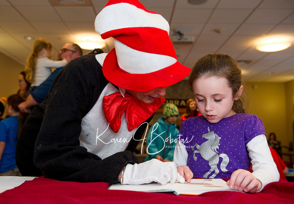 """The Cat in the Hat enjoys reading Sophia's book choice """"I Broke My Trunk"""" by Mo Willems during the Read Across America event at the Gilford Library on Wednesday afternoon.   (Karen Bobotas/for the Laconia Daily Sun)"""