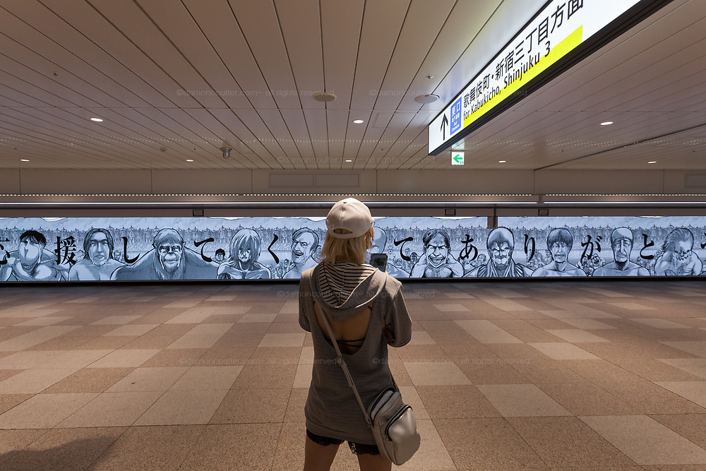 A woman takes a photo of a large LED screen thanking fans of the manga, Attack on Titan,  written and illustrated by Hajime Isayama, for their support over the 12 years the series ran. Shinjuku Station, Tokyo, Japan. Saturday June 12th 2021. The final volume of the series came out on June 9th. The screen features several character busts from the series and is 45.6 metres wide, making it one of largest screens ever made in Japan.