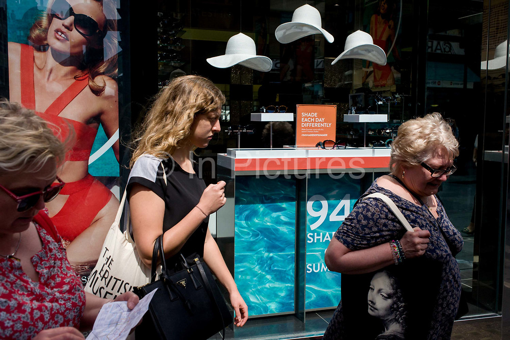 Women consumers walk past a sunglasses shop featuring three hats suspended from the store window ceiling. While one walk along looking down at a central London tube map, the others carry soft bags on their shoulders - one with the face of a classical female figure that echos a modern equivalent of modern woman, seen in the shop's window. The three white hats symbolise a London summer, hanging in clear space above the womens' heads.