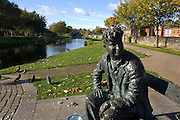 """Bronze casting of writer Brendan Behan, on the Royal Canal, Dublin, by sculptore John Coll. The bench and statue are near Mountjoy Prison, where Behan spent time; his play, the Quare Fellow, features a song called """"The Auld Triangle"""" which mentions the Royal Canal. The casting features triangles..."""