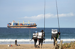South Africa - Durban - 31 August 2020 - Fishermen carrying black and white boxes approach Durban South Beach on Monday afternoon as a big container ship also enters in the harbour<br /> Picture: Doctor Ngcobo/African News Agency(ANA)