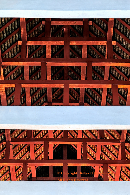 Architectural Symmetry: The red and white wooden ceiling of this Buddhist Temple is an architectural wonder of symmetry, Chiang Mai Thailand.