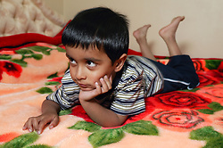 Portrait of young boy lying on the bed watching,