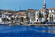 Boats on the quayside bars cafes on historic waterfront buildings, Calvi, Corsica, France in late 1950s