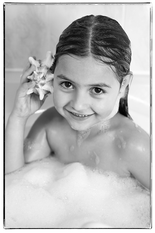 Little girl in her bath, listening to the noise of the sea in a big seashell