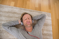Relaxed man lying on rug listening to music