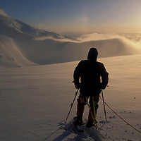 USA, Alaska, Denali National Park, (MR) Rick Ford watches sunset on Kahiltna Glacier during Mt McKinley expedition