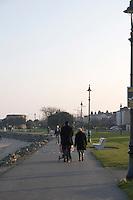 People walking at Sandymount Strand in Dublin Ireland on a winters evening