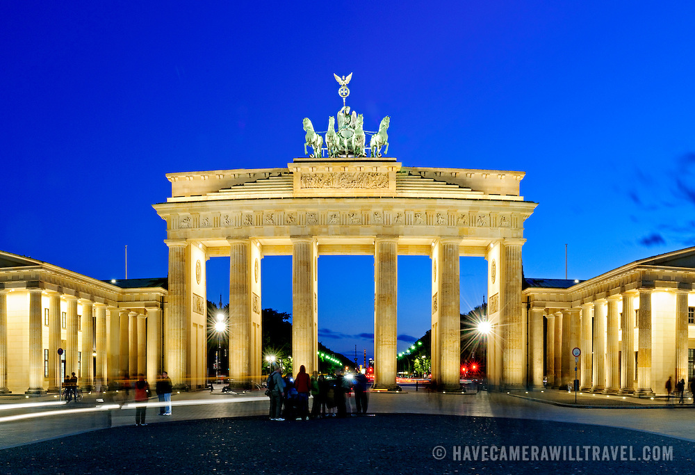 The main structure of the Brandenburg Gate (Brandenburger Tor) in Berlin, Germany, at night with a deep blue sky in the background. A group of tourists stands in the foreground.